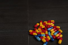 Medicina e tipos coloridos diferentes de comprimidos no fundo preto Fotografia de Stock