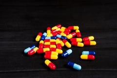 Medicina e tipos coloridos diferentes de comprimidos no fundo preto Imagens de Stock Royalty Free