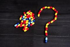 Medicina e tipos coloridos diferentes de comprimidos no fundo preto Fotografia de Stock Royalty Free