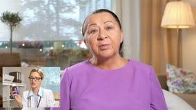 Medicina em linha Mulher idosa que consulta com seu doutor que usa o bate-papo video em casa filme