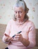 Medicina, età, diabete, sanità e concetto della gente - donna senior con il glucometer che controlla il livello della glicemia a Fotografie Stock