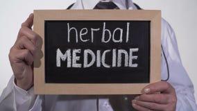 Medicina herbaria escrita en la pizarra en manos del doctor, tratamiento alternativo almacen de video