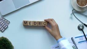 Medicina, la mano de la mujer que hace la palabra de cubos de madera, reforma de la atención sanitaria, visión superior almacen de video