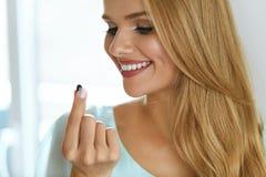 medicina Mujer sonriente hermosa que toma la píldora de la medicación Imagen de archivo libre de regalías