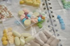 Medicina no saco de plástico claro no fundo do caderno foto de stock