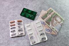 Medicina, píldoras, dinero, en un fondo gris, hryvnia ucraniano Foto de archivo libre de regalías