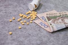 Medicina, píldoras, dinero, en un fondo gris, hryvnia ucraniano Fotos de archivo libres de regalías