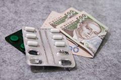Medicina, píldoras, dinero, en un fondo gris, hryvnia ucraniano Imagenes de archivo