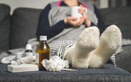 Medicina para el resfriado y mujer enferma que beben la bebida caliente para conseguir f bien foto de archivo