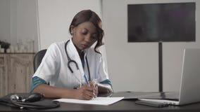Medicina, povos e conceito dos cuidados médicos - doutor ou enfermeira afro-americano fêmea feliz que escrevem o relatório médico imagens de stock