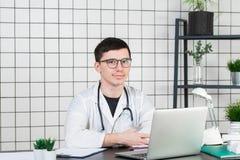 Medicina, profissão, tecnologia e conceito dos povos - doutor masculino de sorriso com o portátil no escritório médico fotografia de stock royalty free