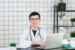 Medicina, profissão, tecnologia e conceito dos povos - doutor masculino de sorriso com o portátil no escritório médico fotografia de stock