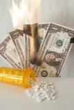 Medicina que desborda la botella con el dinero que quema en fondo Imágenes de archivo libres de regalías