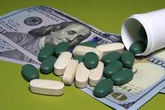 Medicina que se derrama fuera de un paquete en los cientos billetes de dólar Concepto médico del negocio o de los precios imagen de archivo