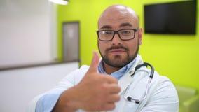 Medicina, sanità e concetto della gente - ritratto di giovane medico maschio sorridente felice che mostra i pollici su archivi video