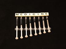 A medicina soletrou para fora com as telhas com as agulhas de graduação da profundidade embaixo em um fundo preto Fotografia de Stock