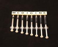 A medicina soletrou para fora com as telhas com agulhas embaixo em um fundo preto Fotografia de Stock Royalty Free