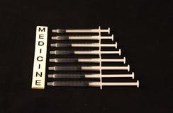 A medicina soletrou para fora com as telhas com agulhas exatamente ao fundo preto Fotos de Stock