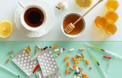 Medicina, té, miel, limón y ajo naturales contra las tabletas de las jeringuillas y de otras medicaciones, fondo de la visión  imagen de archivo libre de regalías