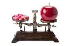 Medicina y una manzana en las escalas Imagen de archivo libre de regalías