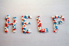 Medicinal capsules form the word help. On wood table Royalty Free Stock Images