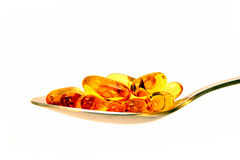 Medicinal capsules in metal spoon Stock Images