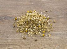 Medicinal chamomile herbs. On wood background Royalty Free Stock Photo
