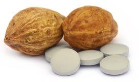 Medicinal Haritaki fruits with tablets Royalty Free Stock Photos