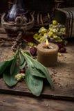 Medicinal herb and burning candle Stock Photo