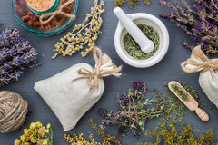 Medicinal herbs, mortar, sachet and bottle of drugs. Medicinal herbs, mortar of healing herbs, sachet and bottle of healthy drugs on wooden table. Herbal Stock Image