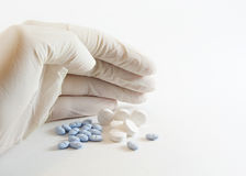 medicinal pills för behandskad hand Arkivbild