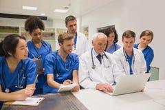 Medicinare och professor som använder bärbara datorn arkivfoto