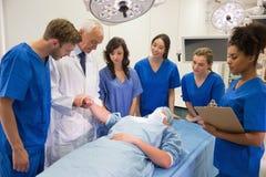 Medicinare och professor som kontrollerar puls av studenten Royaltyfria Foton