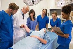 Medicinare och professor som kontrollerar puls av studenten Arkivbilder
