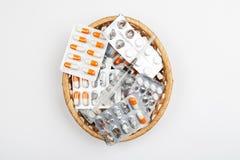 Medicinas en paquetes de ampolla en una cesta de mimbre en un fondo blanco foto de archivo libre de regalías