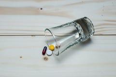Medicinas en una tabla de madera en vidrio minúsculo Fotos de archivo