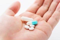Medicinas y tabletas azules de la cápsula en la mano masculina imagenes de archivo