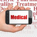 Medicinbegrepp: Hand som rymmer Smartphone med läkarundersökning på skärm Arkivfoton