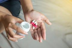 Medicindrog förestående, kvinnahand med preventivpillerar på spill av preventivpillerar ut ur flaskan Royaltyfri Fotografi