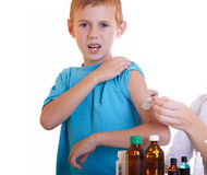 Medicine. The doctor tears off a plaster by hand the boy Stock Photo