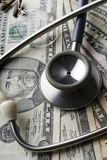 Medicine. A stethoscope and a pair of rimless glasses on various US bills Stock Photography
