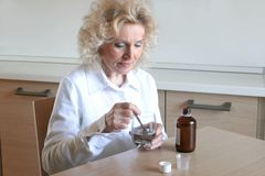 Medicine 44. A senior woman with a glass and a medicine Stock Photography