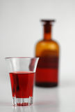 Medicine. Old-fashioned flask with glass of medicine on the foreground royalty free stock photography