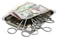 Medicine. Surgical tools and money in a steel tray. It is isolated on a white background Stock Photos