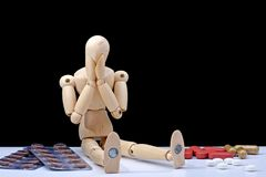 Medicine addiction. Wooden mannequin, feeling very bad (about his medicine addiction Royalty Free Stock Photography