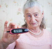 Medicine, age, diabetes, health care and people concept - senior woman with glucometer checking blood sugar level at Royalty Free Stock Photography