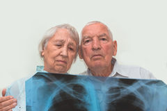 The medicine, age, health care and people concept - the sad senior woman and man looking at cardiogram on gray. The medicine, age, health care and people concept Royalty Free Stock Images