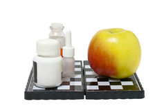Medicine and an apple on a chessboard Stock Images