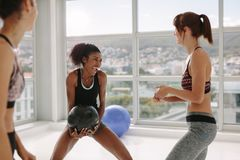Medicine ball group exercise at gym. Smiling women doing medicine ball group exercise at gym. Woman passing the exercise ball to a female standing by in fitness stock image