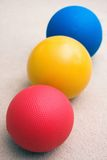 Medicine balls sitting in a line. Red, yellow, and blue medicine balls sitting in a row in a pilates gym Stock Photo